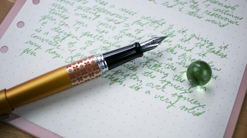 Pen laying next to green marble on paper with green writing.