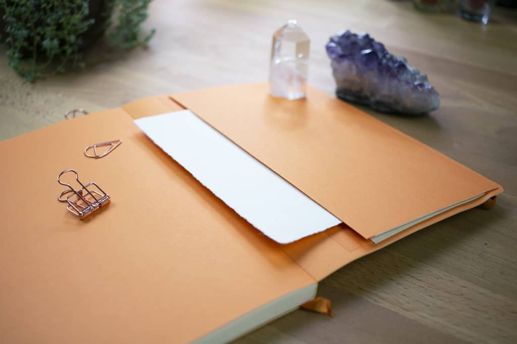 A Rhodia notebook open to the back cover to display the expandable pocket.