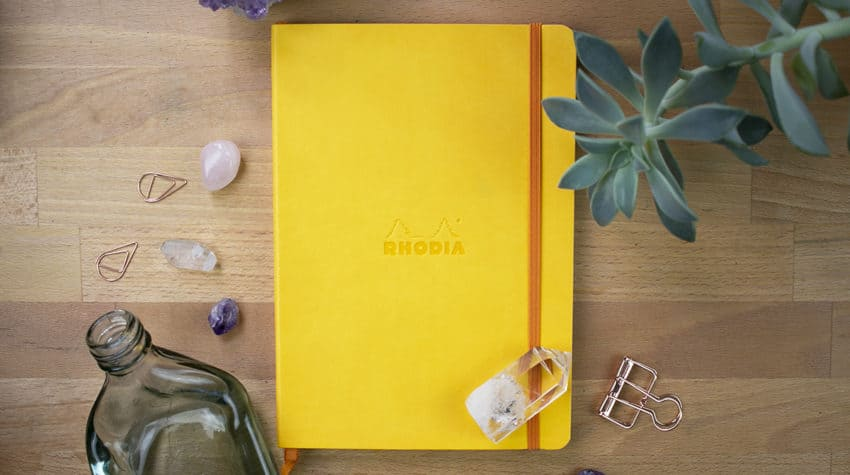 A closed yellow Rhodiarama notebook sitting on a desk.