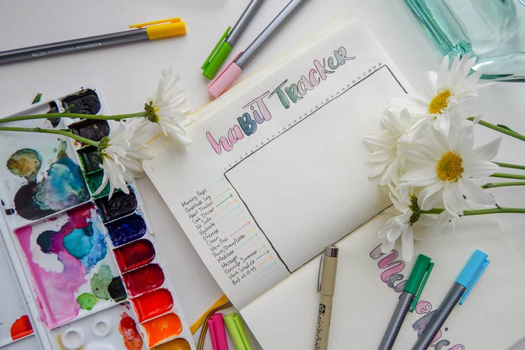 Open journal with habit tracker embellished with watercolor lettering, with watercolor palette nearby and flowers laying on desk.