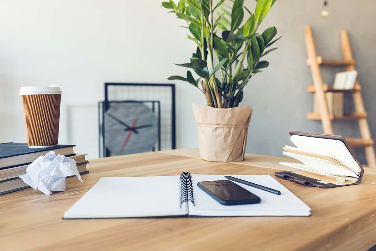 Photo of wood desk with plant, clock, coffee mug, planner, and phone.