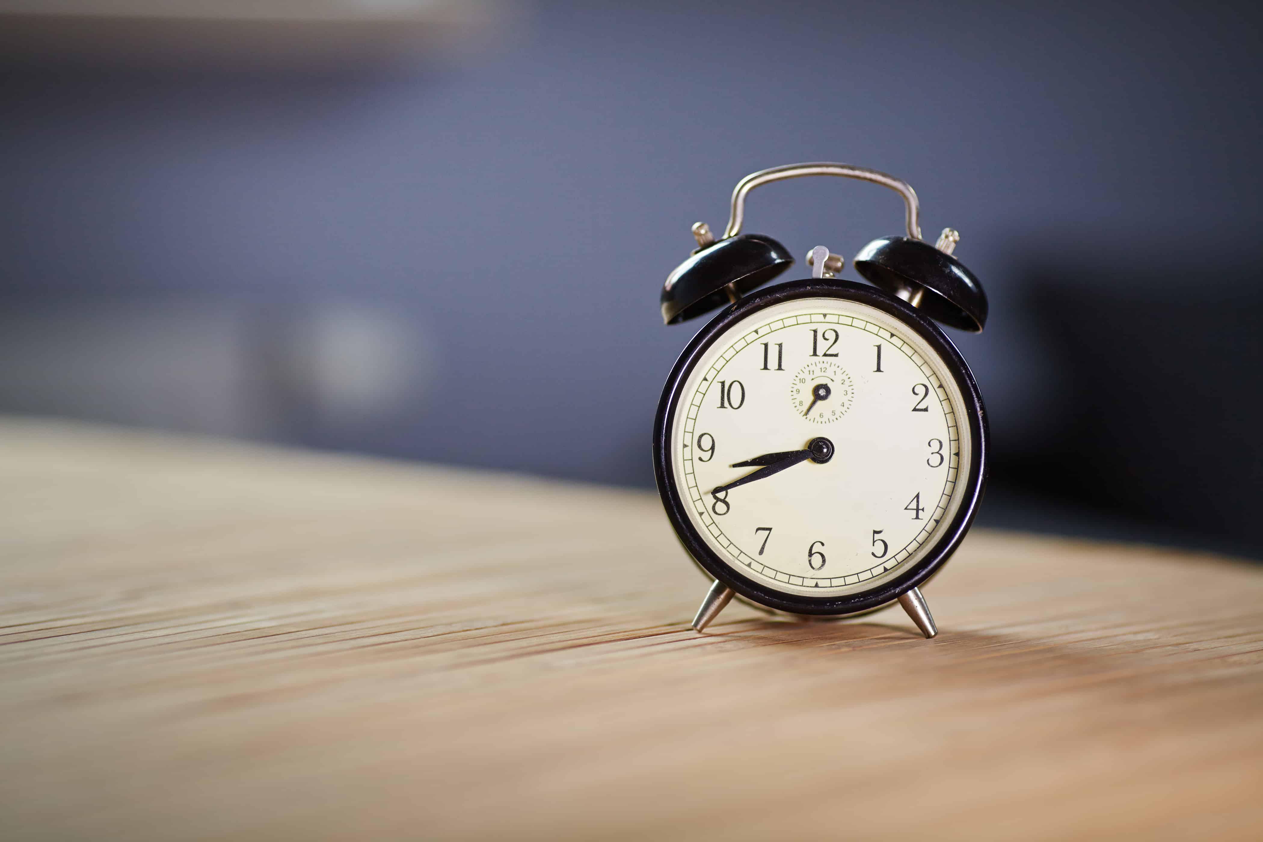 Retro alarm clock on desk front grey wall background