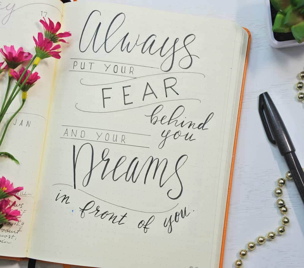 "A hand lettered inspirational quote about how to overcome procrastination. ""Always put your fear behind you and your dreams in front of you"""
