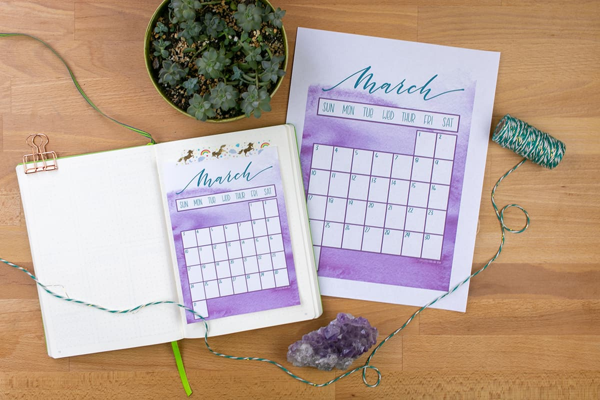 Bird's eye view of full sized March printable and A5 sized printable on a desk.
