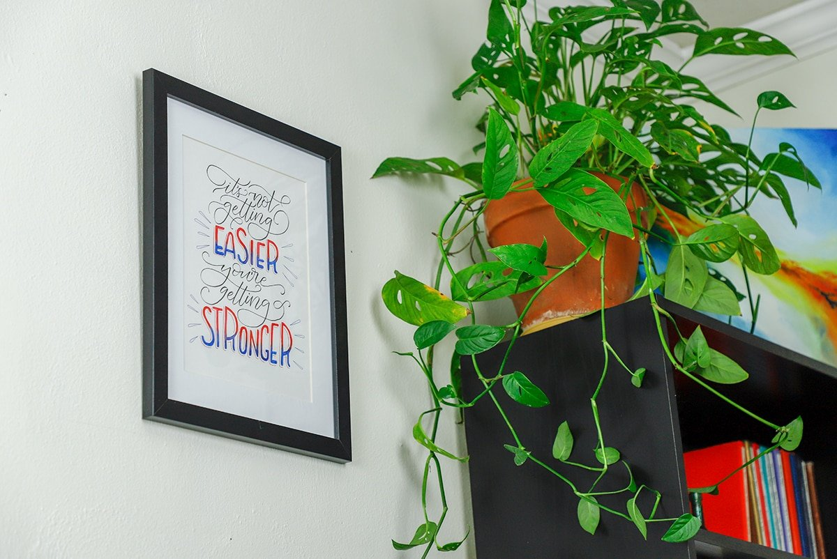 Watercolor brushed quote framed and hanging on wall with plant.