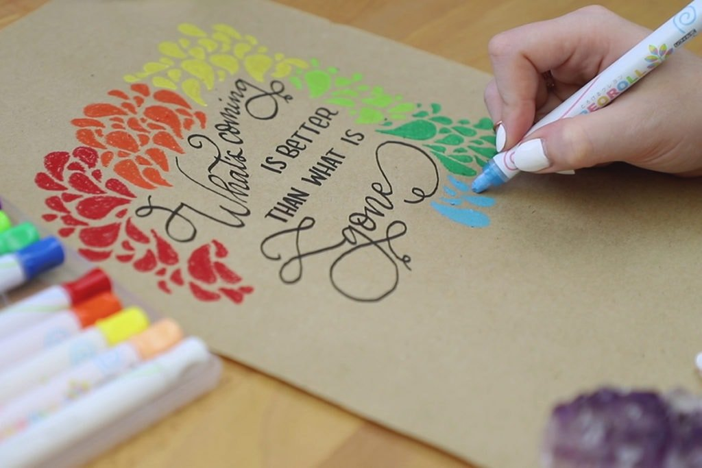 Hand drawing colorful abstract pattern around lettering.