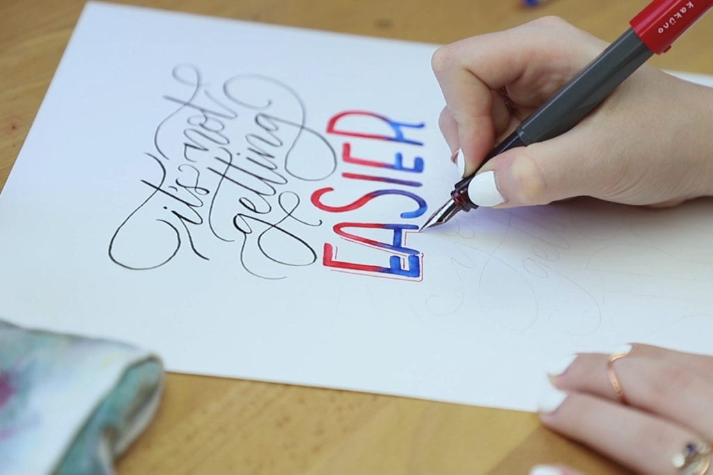 Hand adding drop shadow to letters.