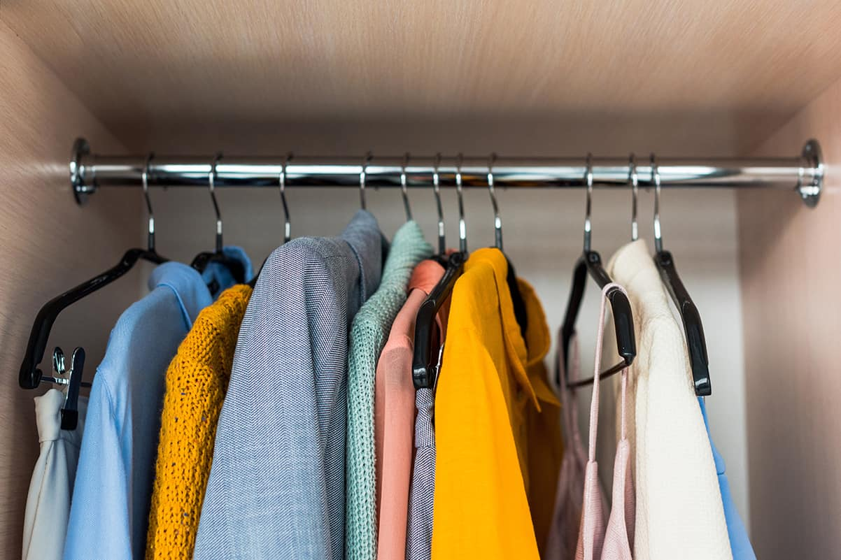 Yellow and blue clothes hanging in wardrobe