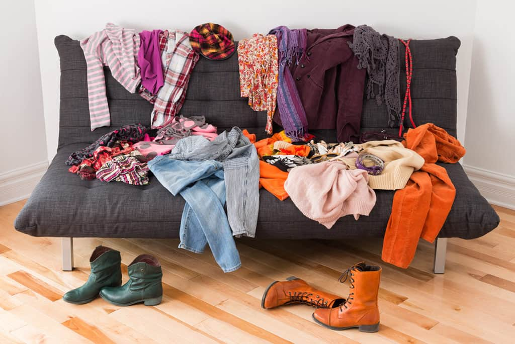 Couch covered in myriad of clothing, demonstrating how clutter can get in the way of simplifying your life
