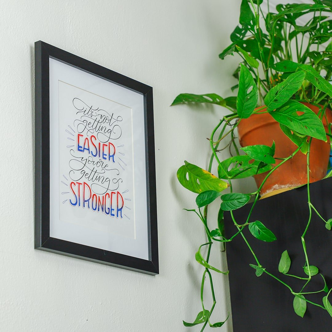 Watercolor brushed DIY wall art framed and hanging on wall with plant.