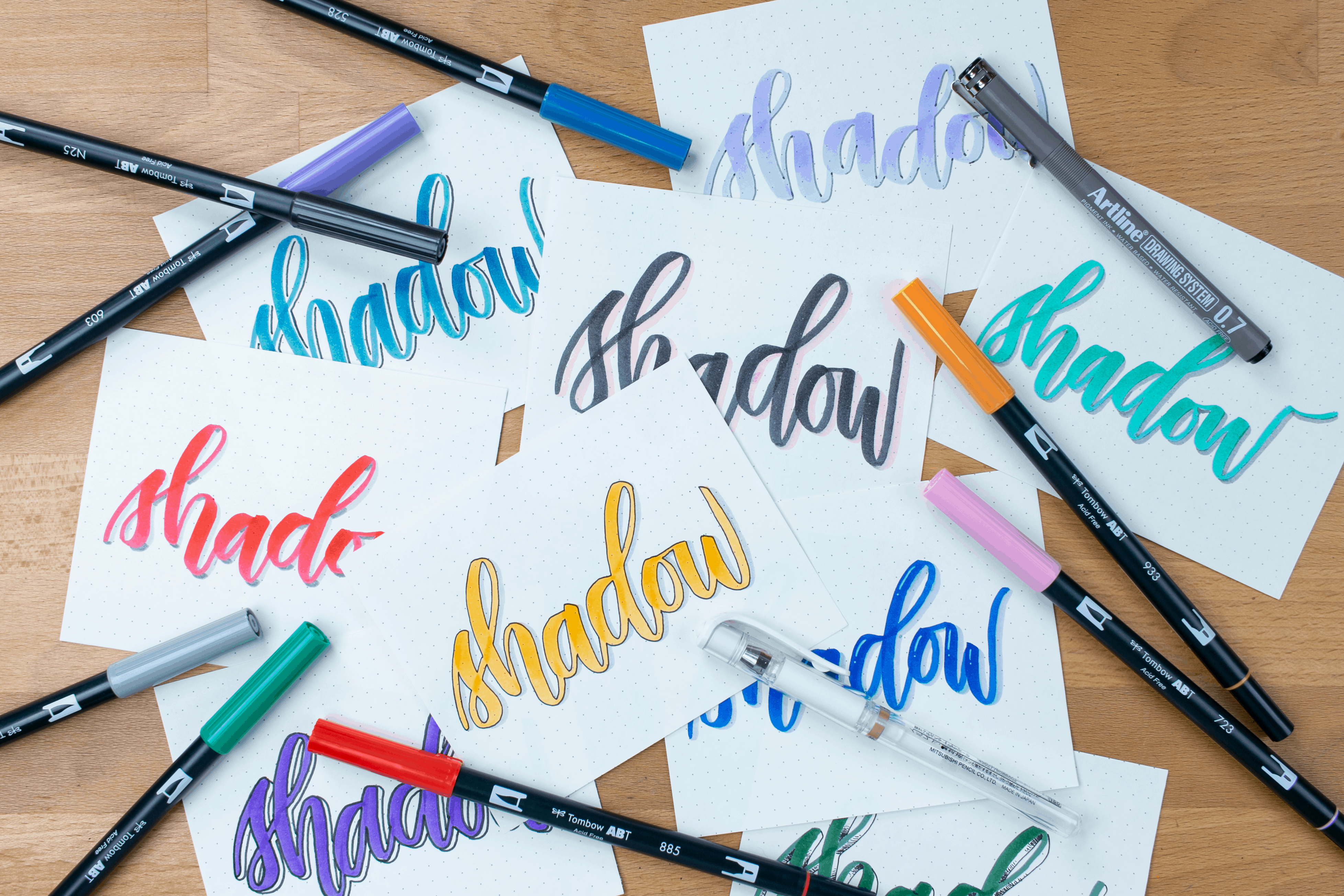 Pile of all brush lettering shadows examples with pens on desk.