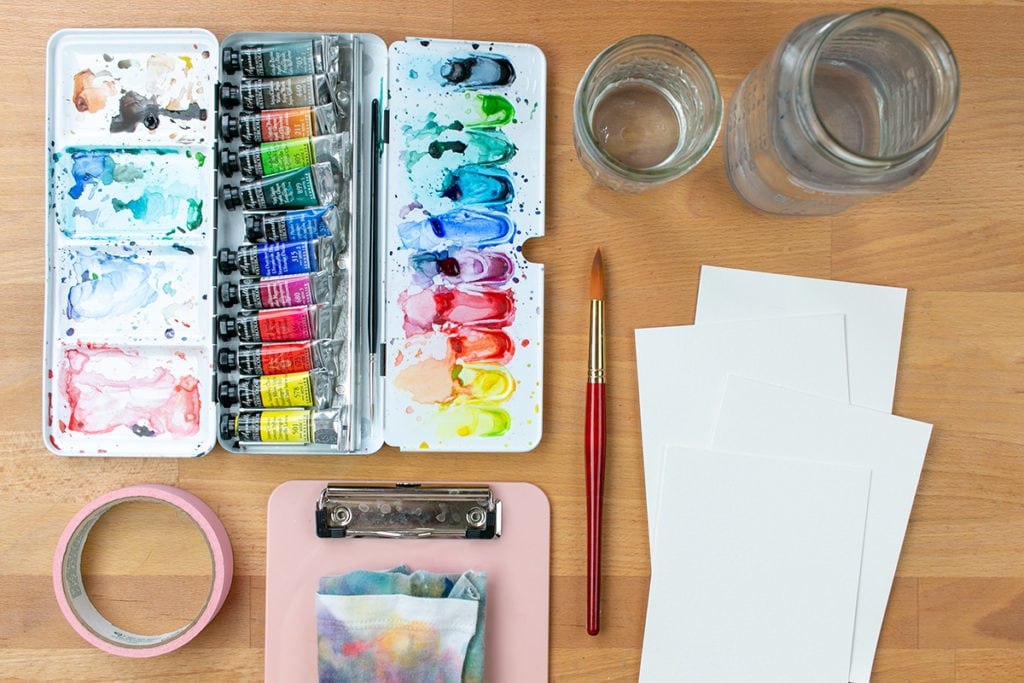 Watercolor wash tools laid out on a desk, including a watercolor palette with paints, a brush, tape, water jars, blank paper, a clipboard, and a rag.