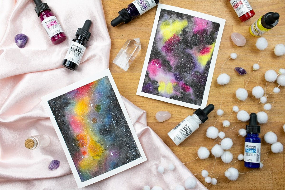 Two watercolor galaxies on a table with art supplies