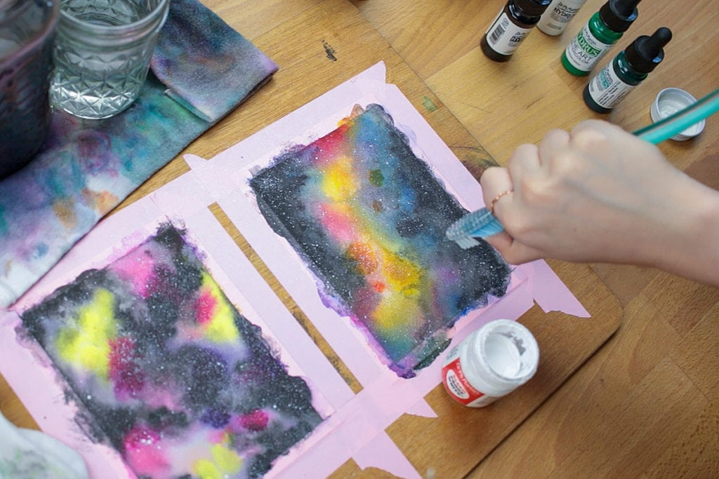 Flick white paint with a toothbrush to add stars to your watercolor galaxy