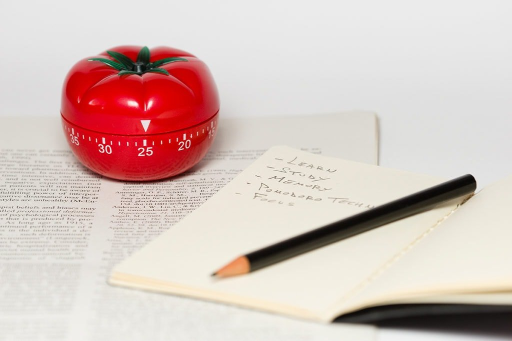 A Pomodoro timer on a desk with an open notebook