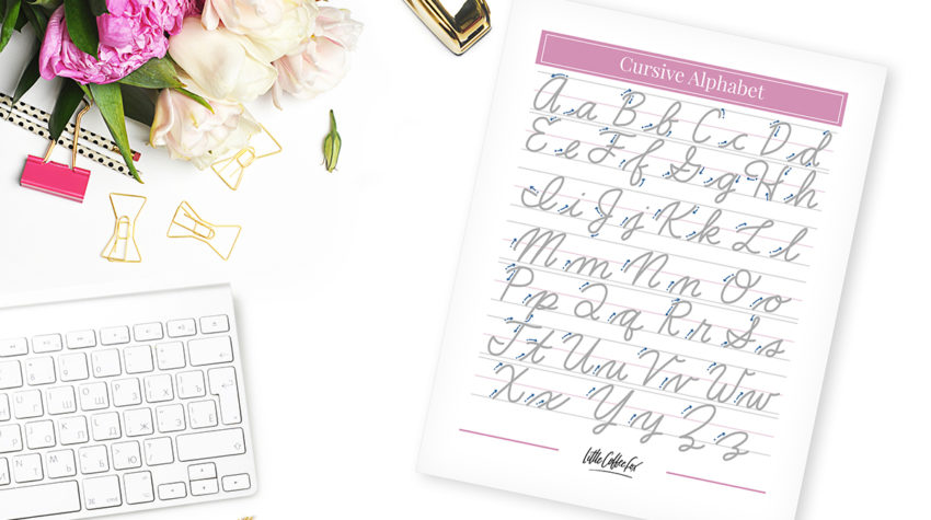 Cursive letters worksheet on white desk with flowers.