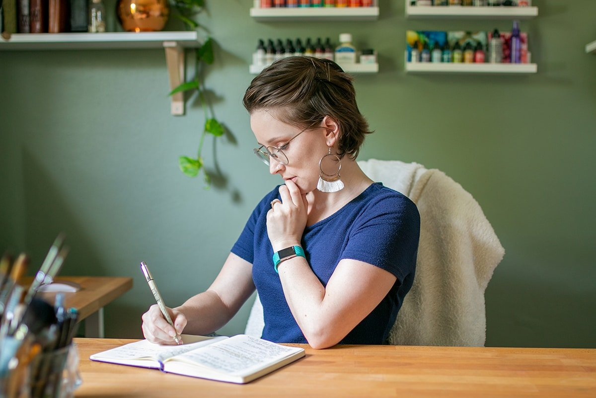 Picture of Shelby at her desk with a journal open.