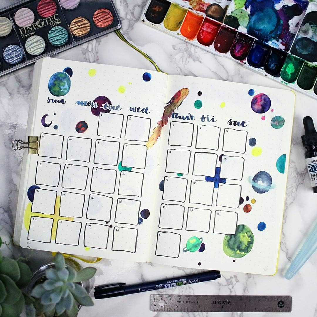 A bullet journal monthly spread depicting planets and stars