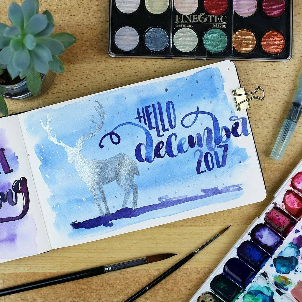 A December Monthly Spread of a deer done with blue watercolors depicting a wintry scene