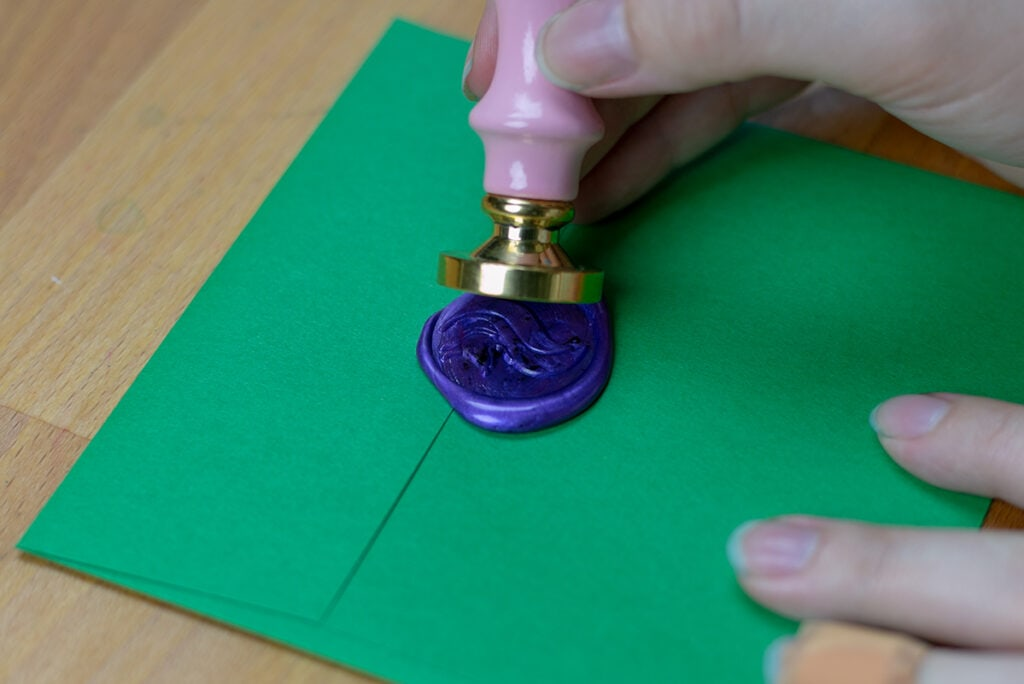 Removing stamp to reveal fox wax seal on envelope