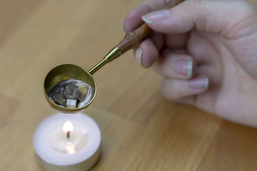 Melting wax beads in spoon over tealight.