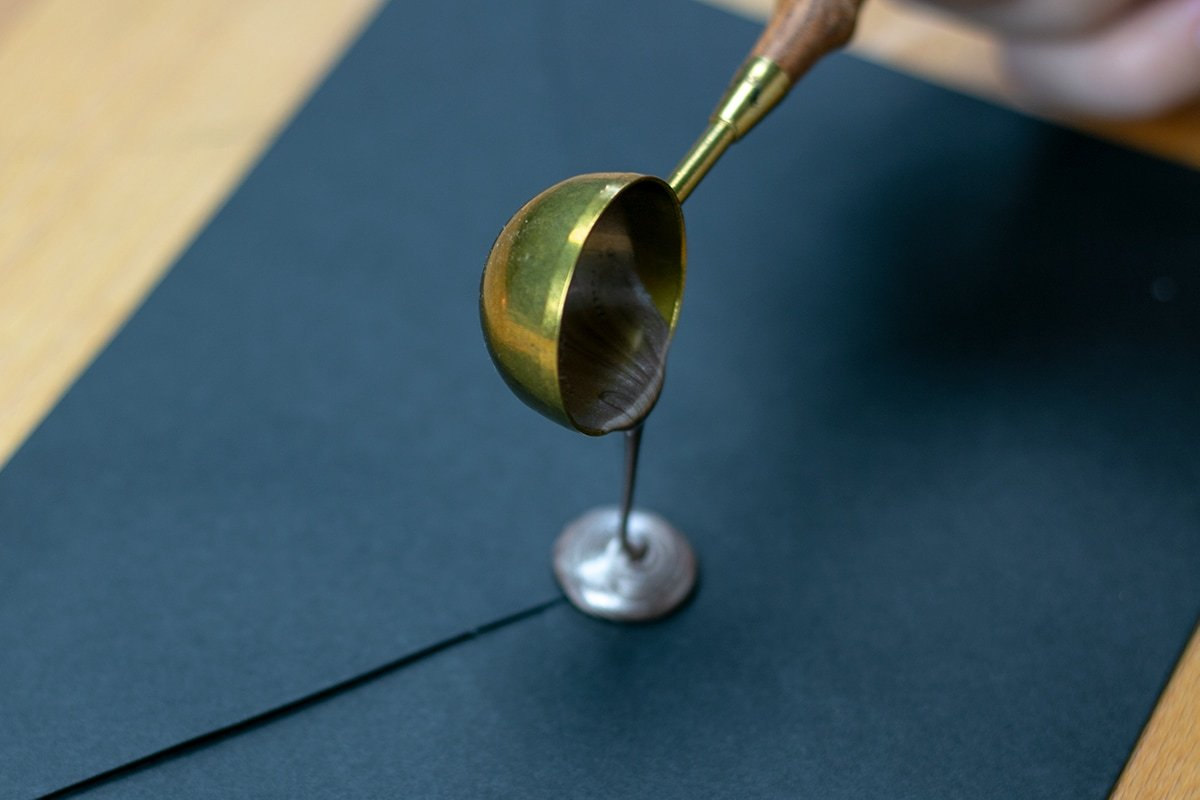 Sealing wax pouring from spoon onto black envelope.