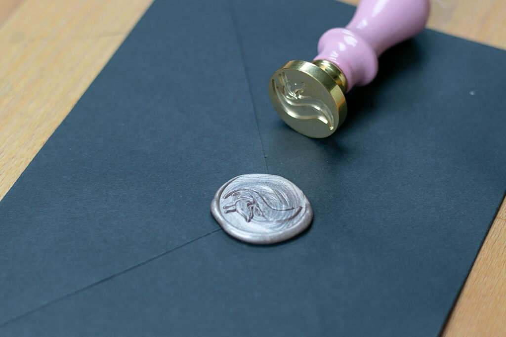 Champagne wax seal with Little Coffee Fox logo on black envelope.