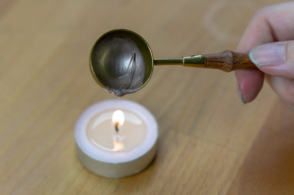 Reheating the hardened wax in the spoon over a tealight