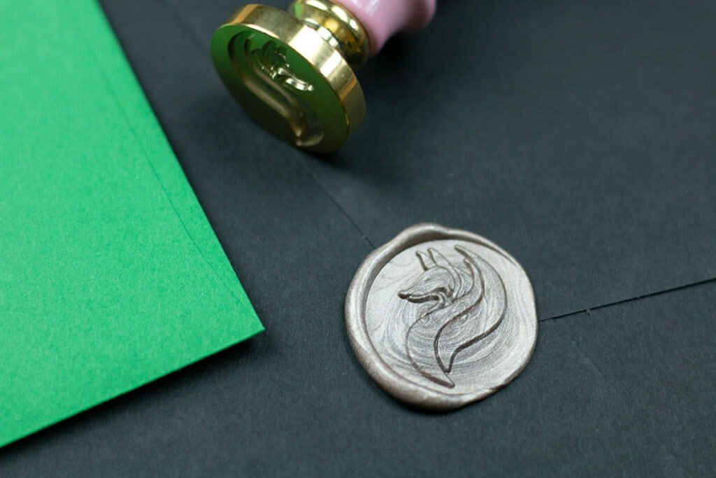 Close shot of Little Coffee Fox logo in champagne wax seal on black envelope.