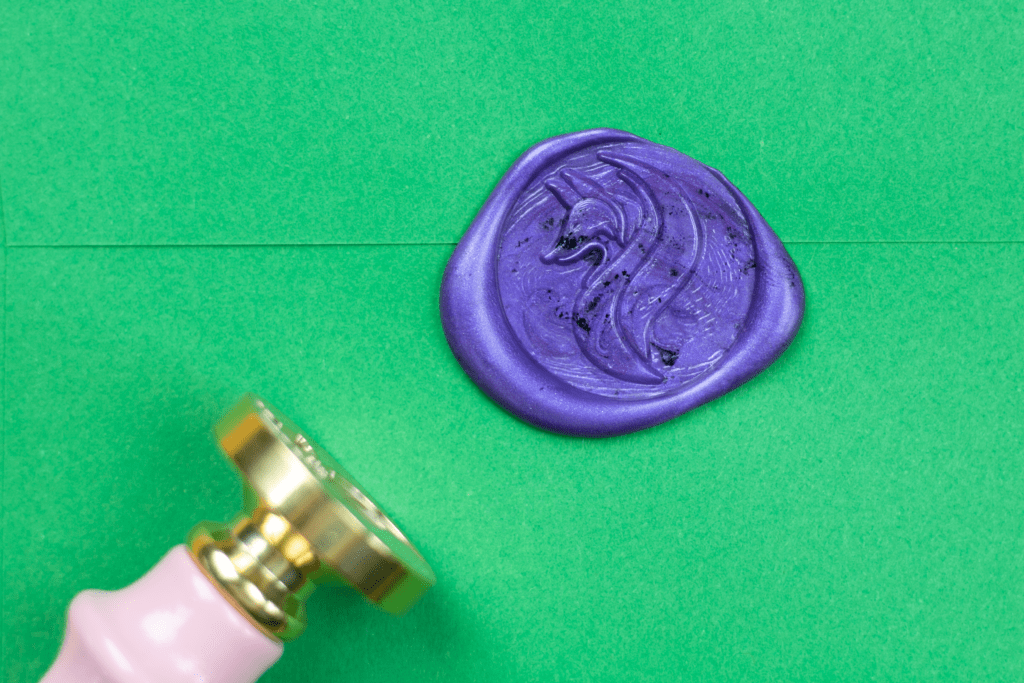 Close up shot of purple wax seal on green envelope with Little Coffee Fox logo in wax