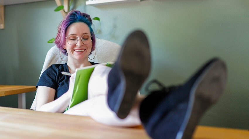 Image of Shelby sitting at her desk with her legs kicked up and journal in her lap.