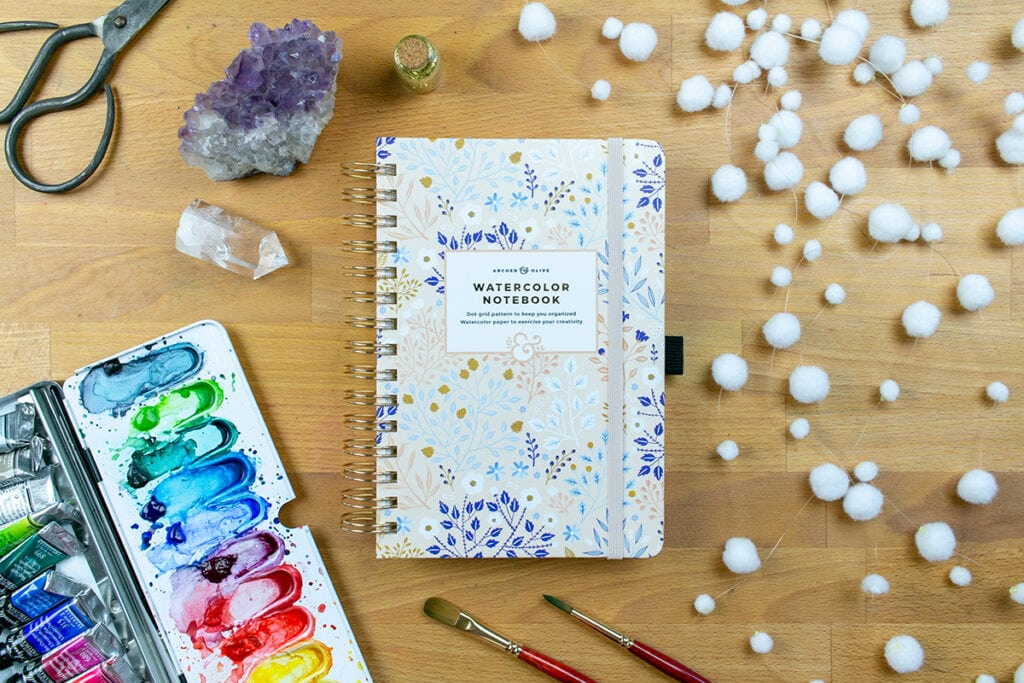 Archer & Olive Watercolor Dot Grid Journal laying on table with watercolors