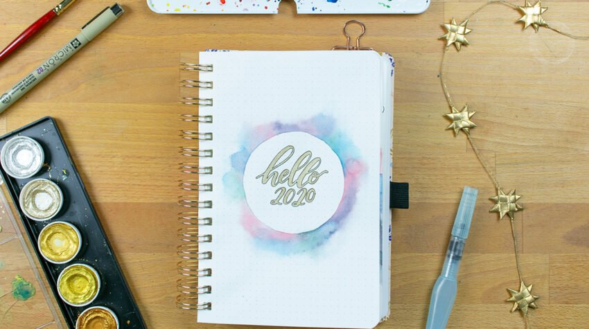 "Page with gold ""hello 2020"" on desk with art supplies"