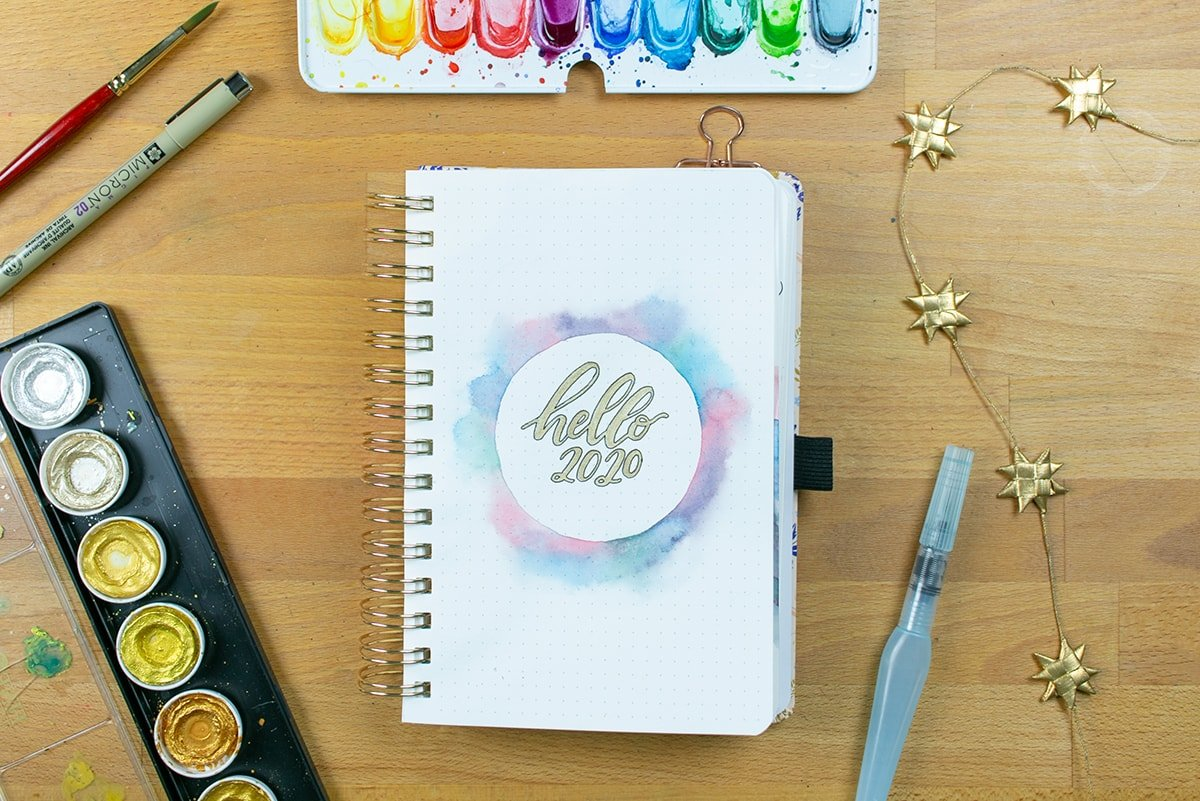 """Page with gold """"hello 2020"""" on desk with art supplies"""