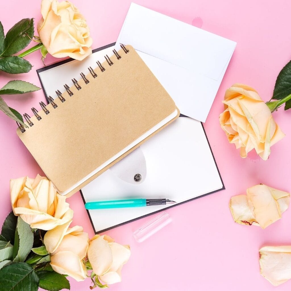 yellow roses and bullet journal with bullet journal pen laying on a pink background