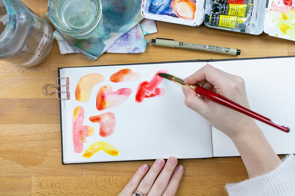 Hand painting red watercolor blobs on page.