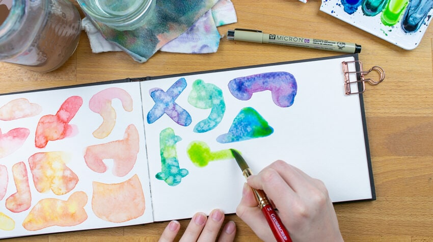 Hand painting blue and green watercolor blobs on page
