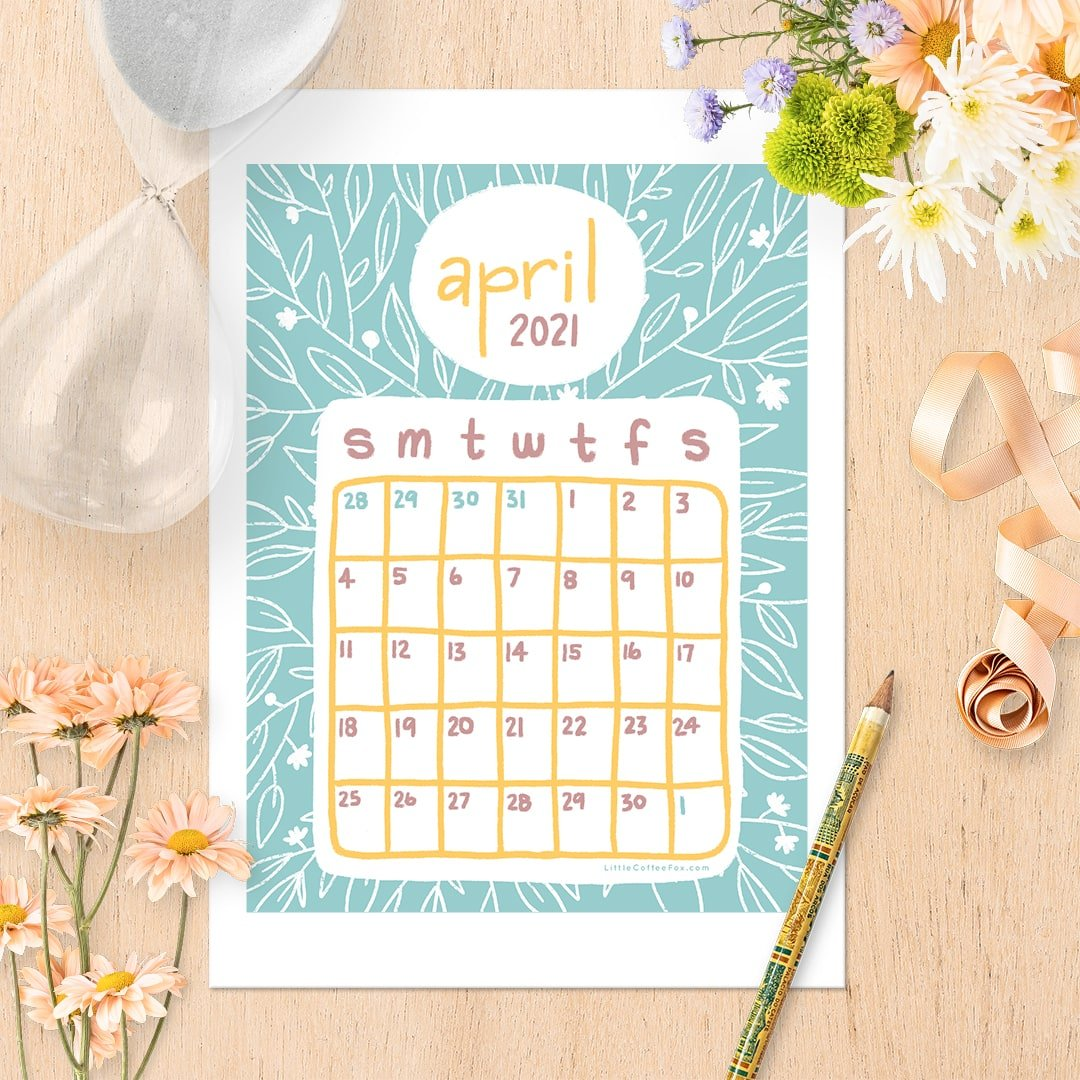 April calendar printable on desk with flowers, and hourglass, a ribbon, and pencil sitting nearby.