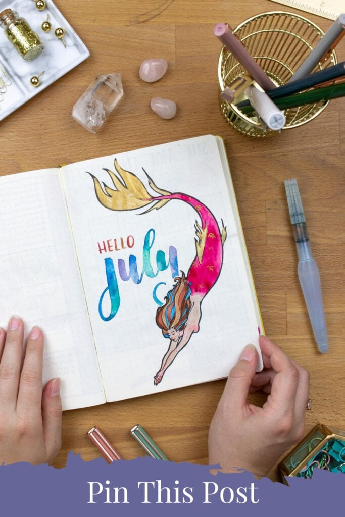 """An overhead image of the bullet journal cover page with a mermaid. Text across the bottom of the image saying """"Pin This Post"""""""