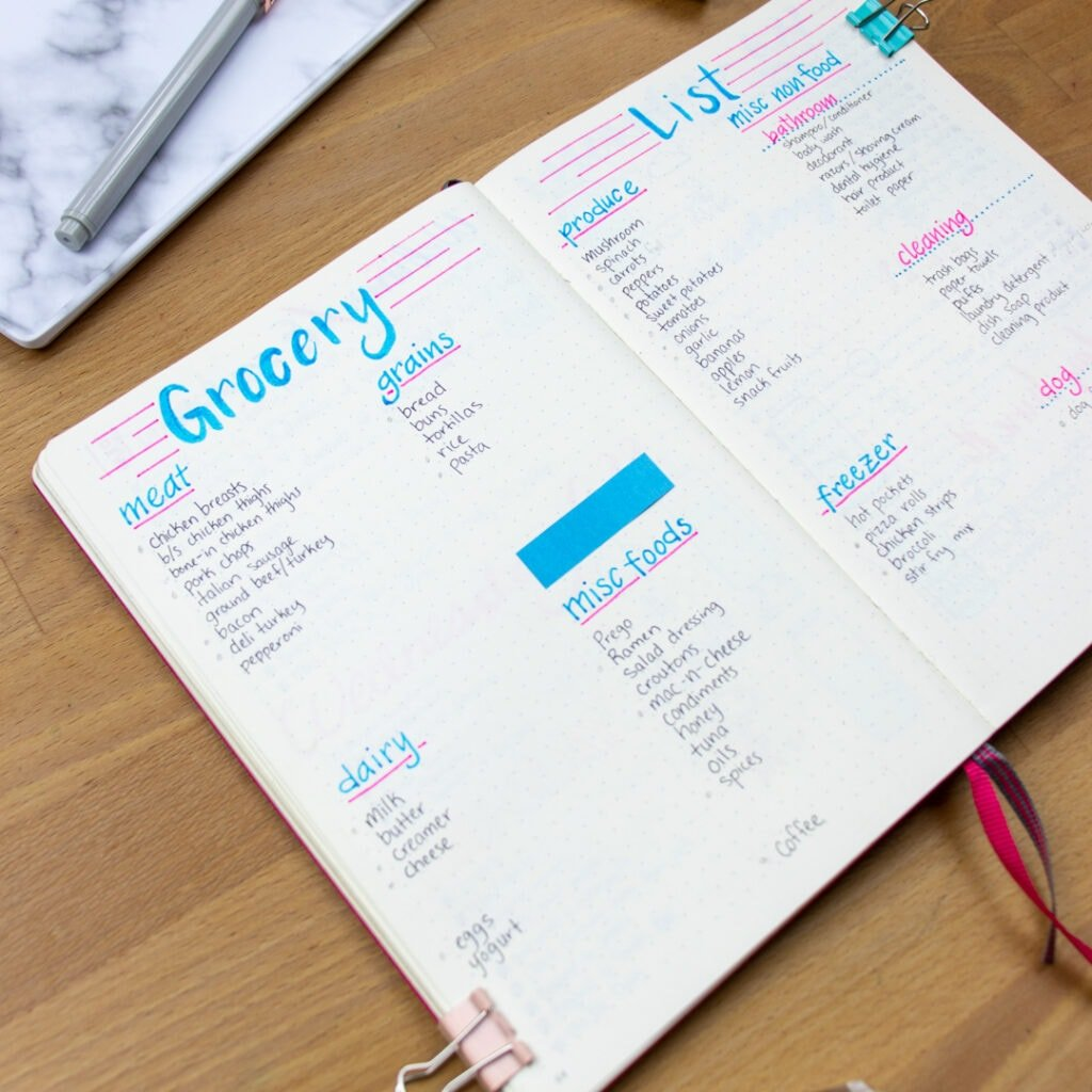 The left page of a bullet journal is open, titled 'Grocery'. The words are written in blue ink and are underlined in pink ink. There are sections for meat, grains, dairy, and miscellaneous foods. The book is tilted slightly to the left.