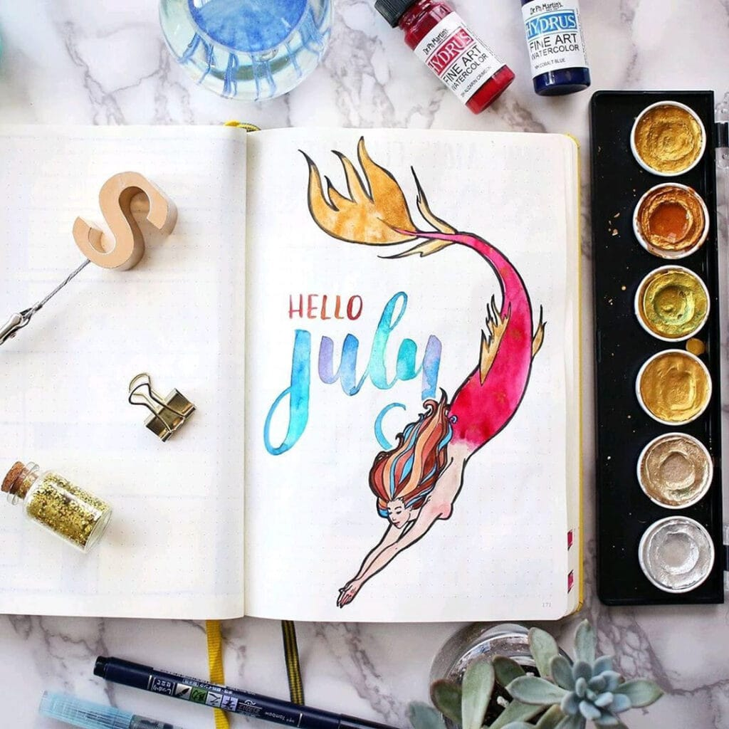 An overhead view of a watercolor mermaid cover page.