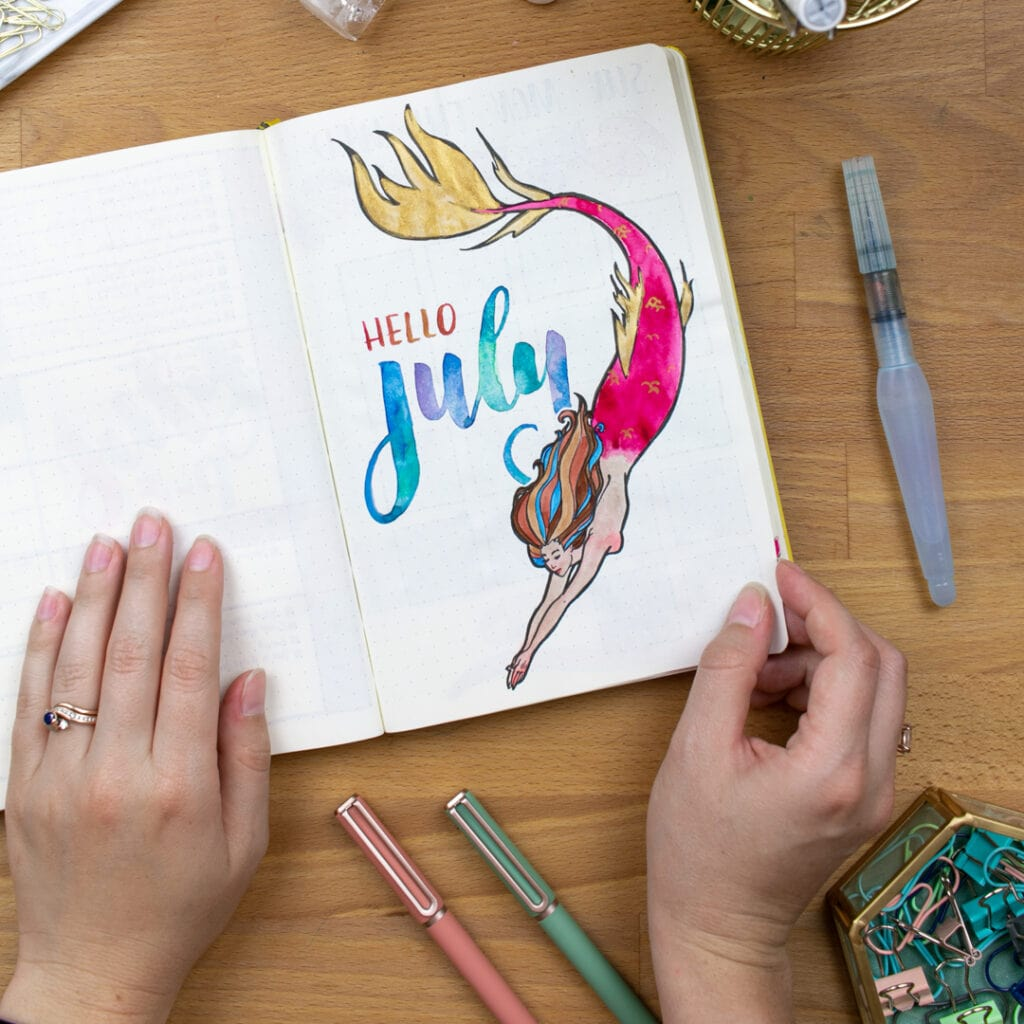 """An overhead view of my mermaid bullet journal cover page with a watercolor mermaid and """"Hello July"""" written in watercolor."""
