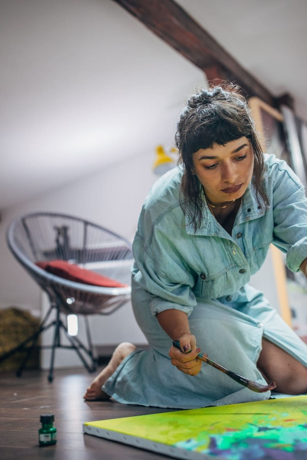 image of harmful myths about artists with woman painting on a canvas sitting on the floor