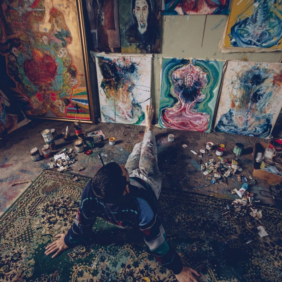 man sitting in front of his paintings