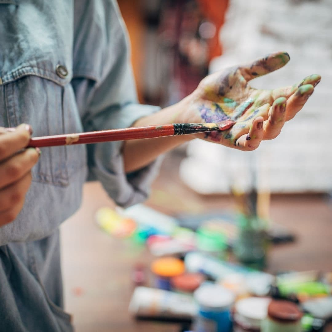harmful myths about artists image of an artist with paint brush and paint on her hands