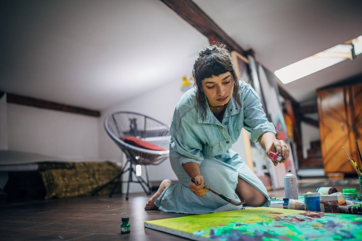 woman painting on a canvas on the floor