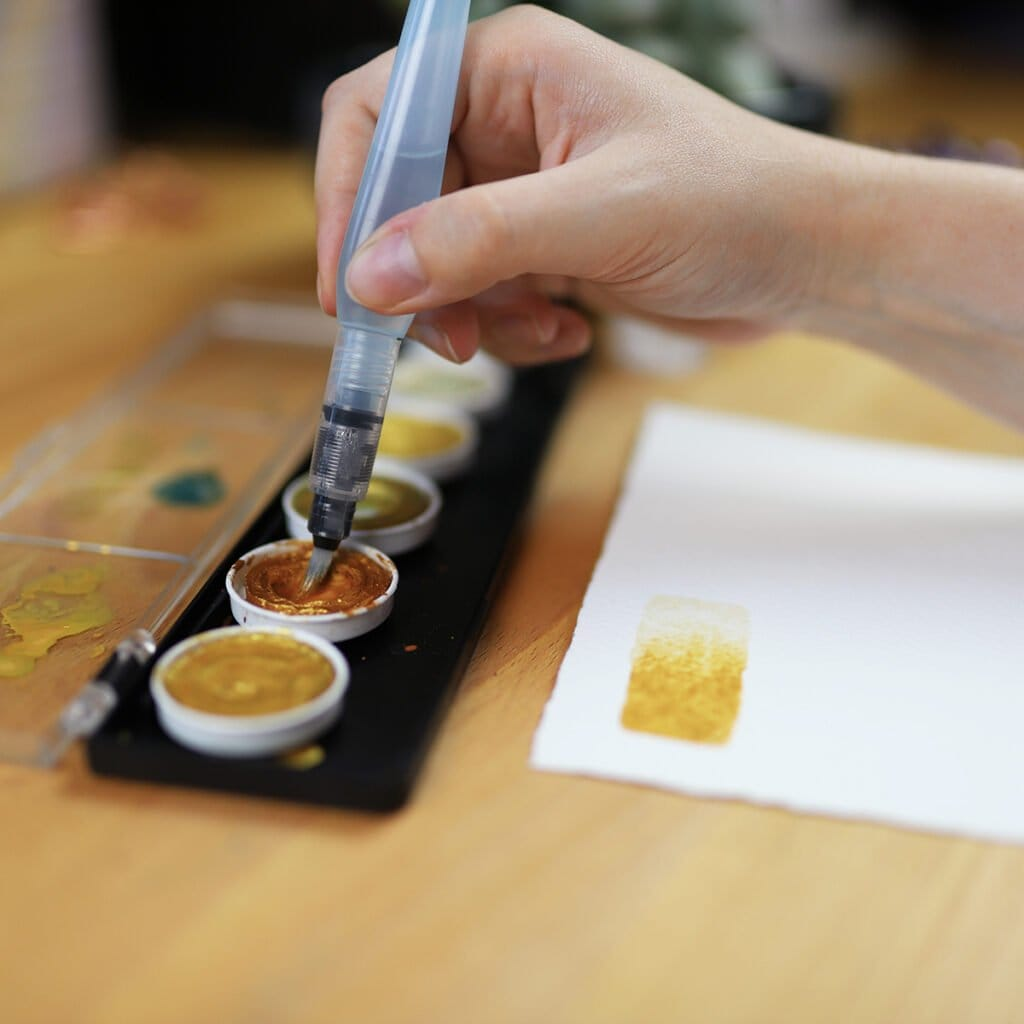 Hand dipping brush in pan of gold watercolor.