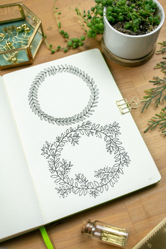 Journal open to two illustrations of wreaths.