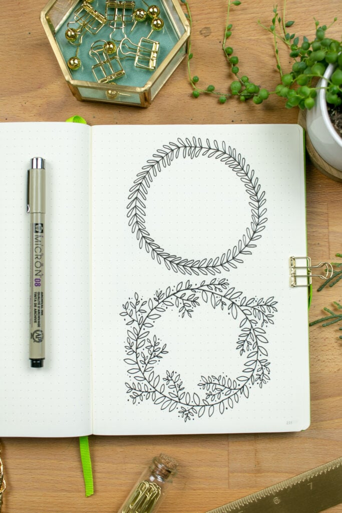 Overhead shot of journal open to two illustrations of wreaths.