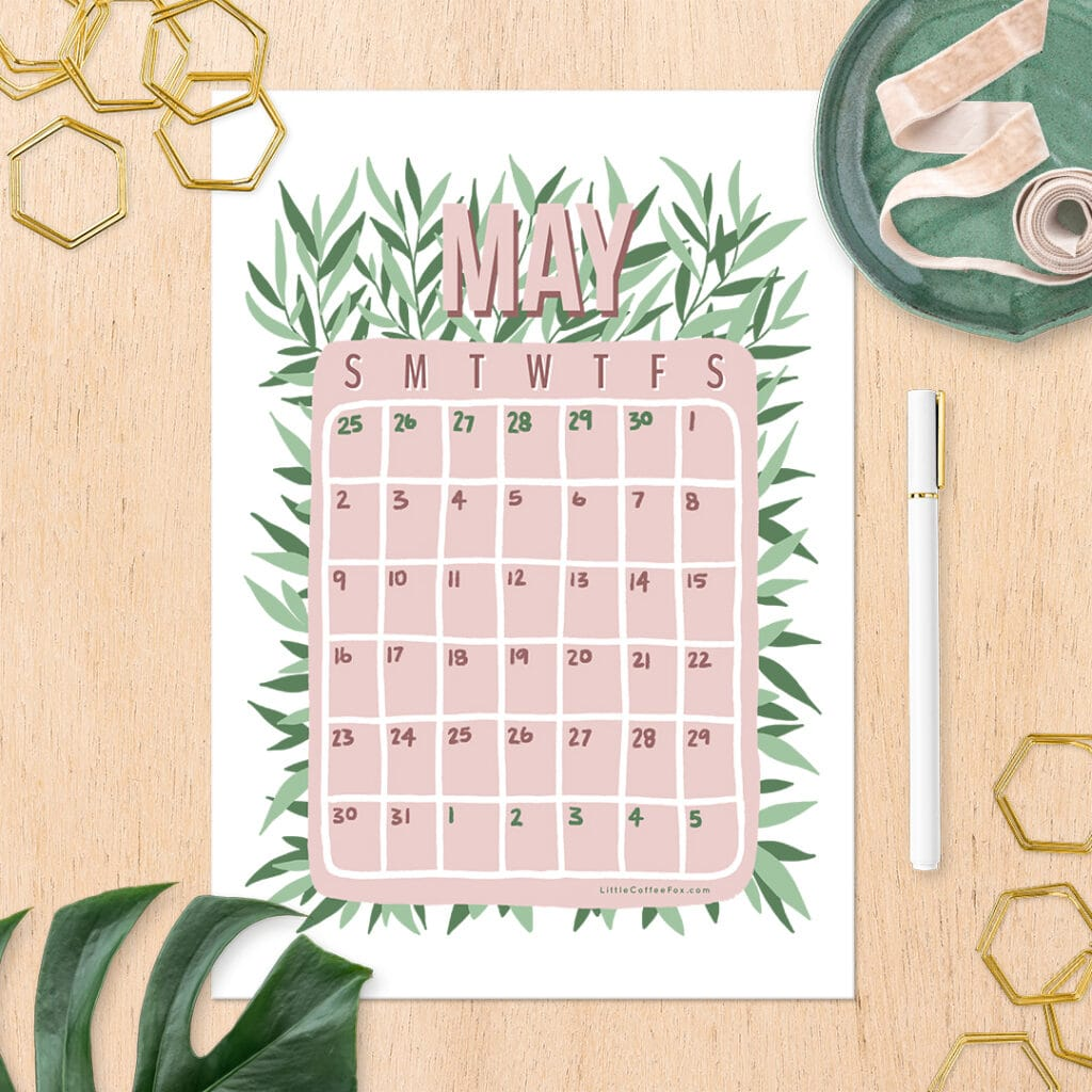 May 2021 calendar printable on a wooden desk with golden hexagonal paperclips, a green dish with pink ribbon inside, a monstera leaf, and a white pen.